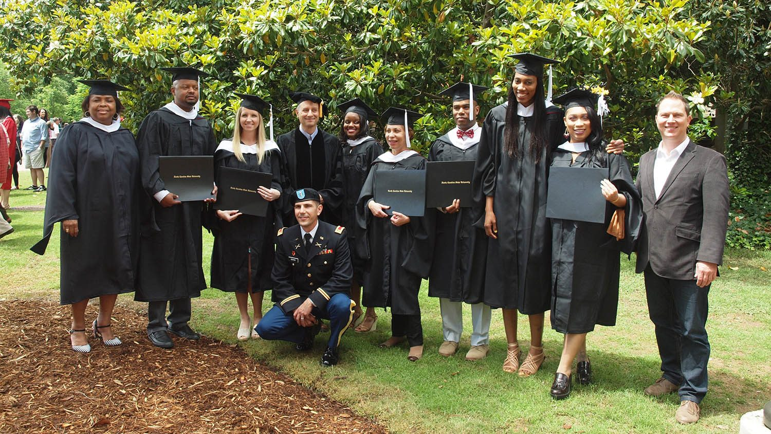 group of graduates stand with Seth Murray