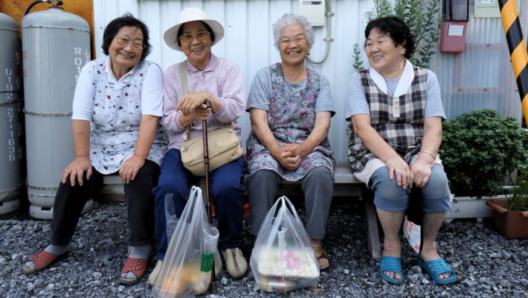 Four women sit on a bunch and smile