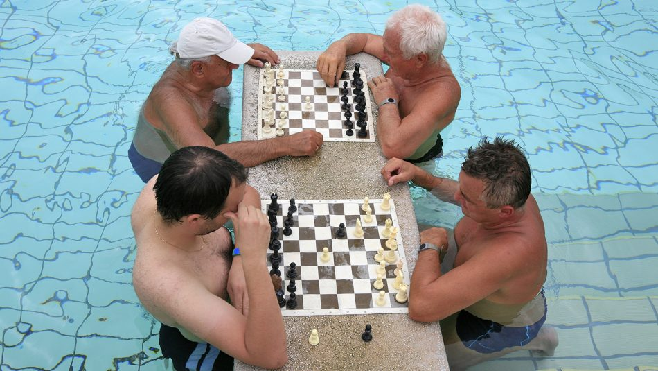 Four men play chess while sitting in a pool