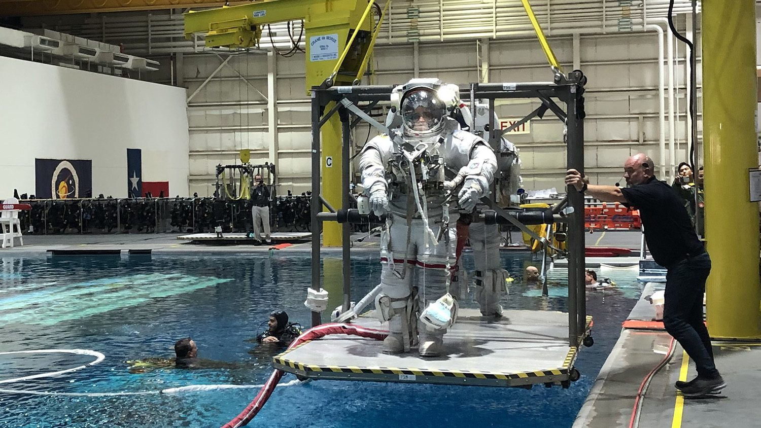 astronaut prepares to go into pool of water