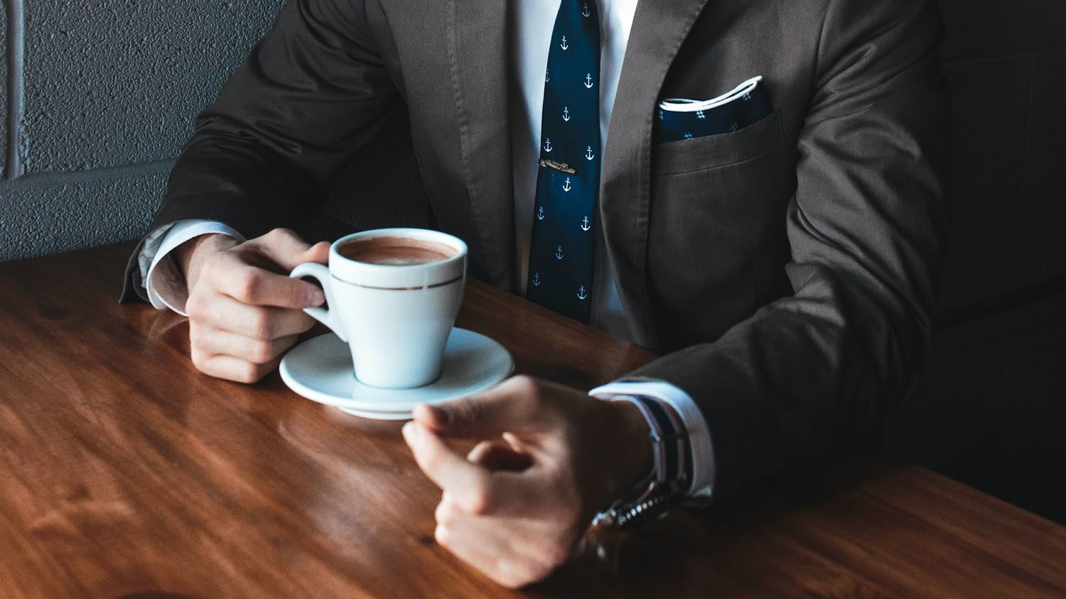 man wearing suit holds coffee cup