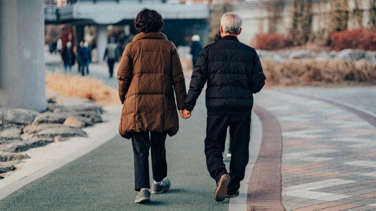an older couple walks down the street