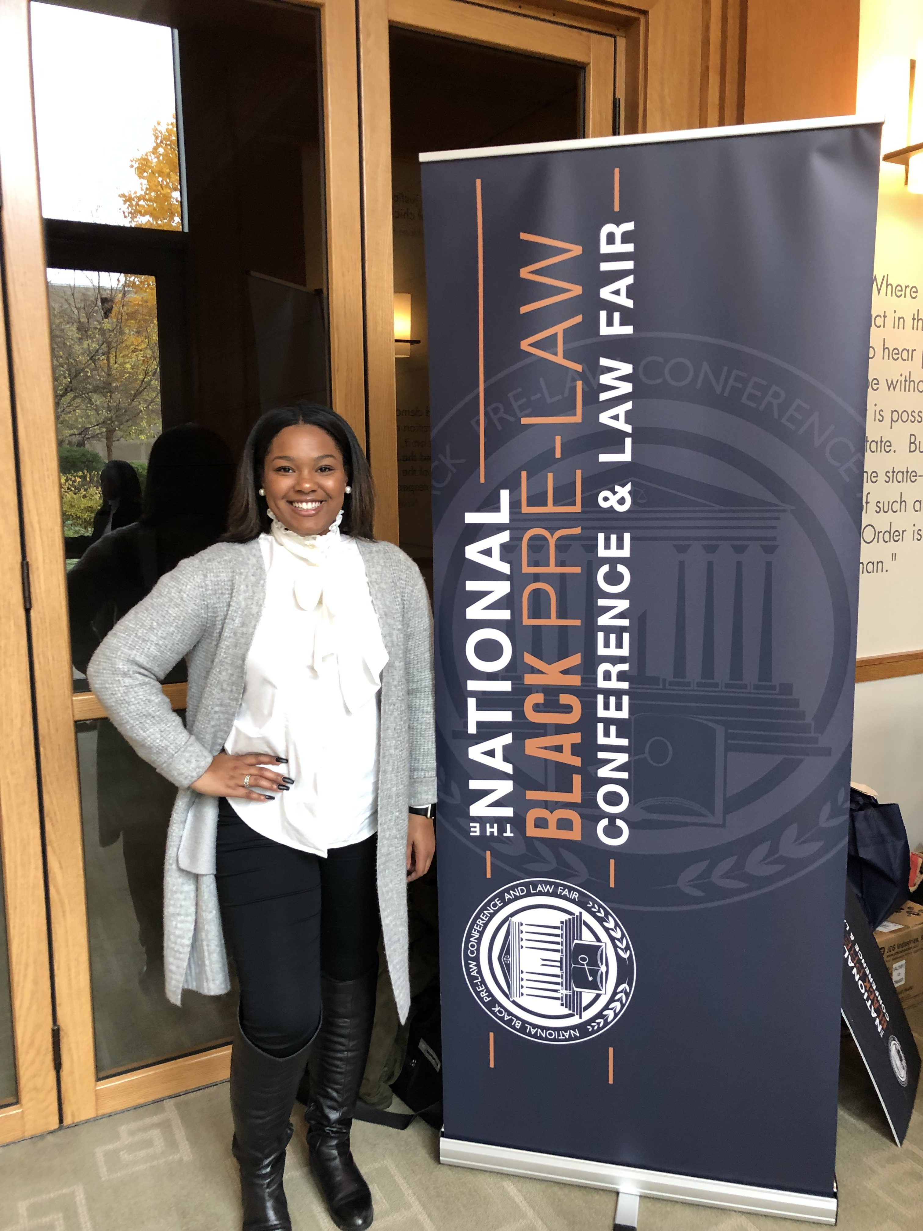 Malasia McClendon in front of a conference sign.