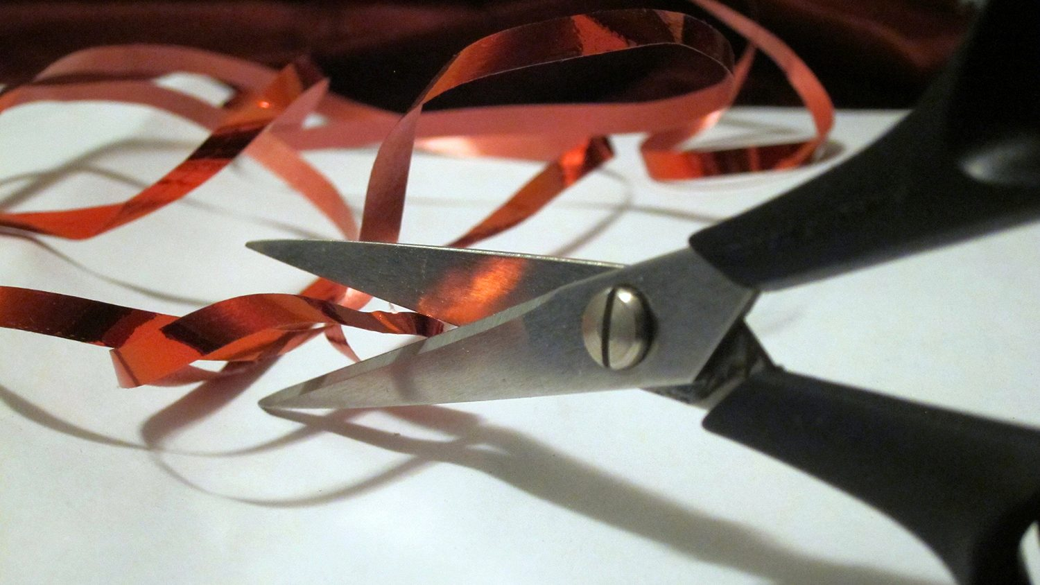 Scissors prepare to cut through a tangle of yarn
