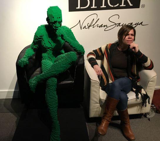Erica Edwards sitting next to sculpture of man in thinking pose made of green Legos by Nathan Sawaya.