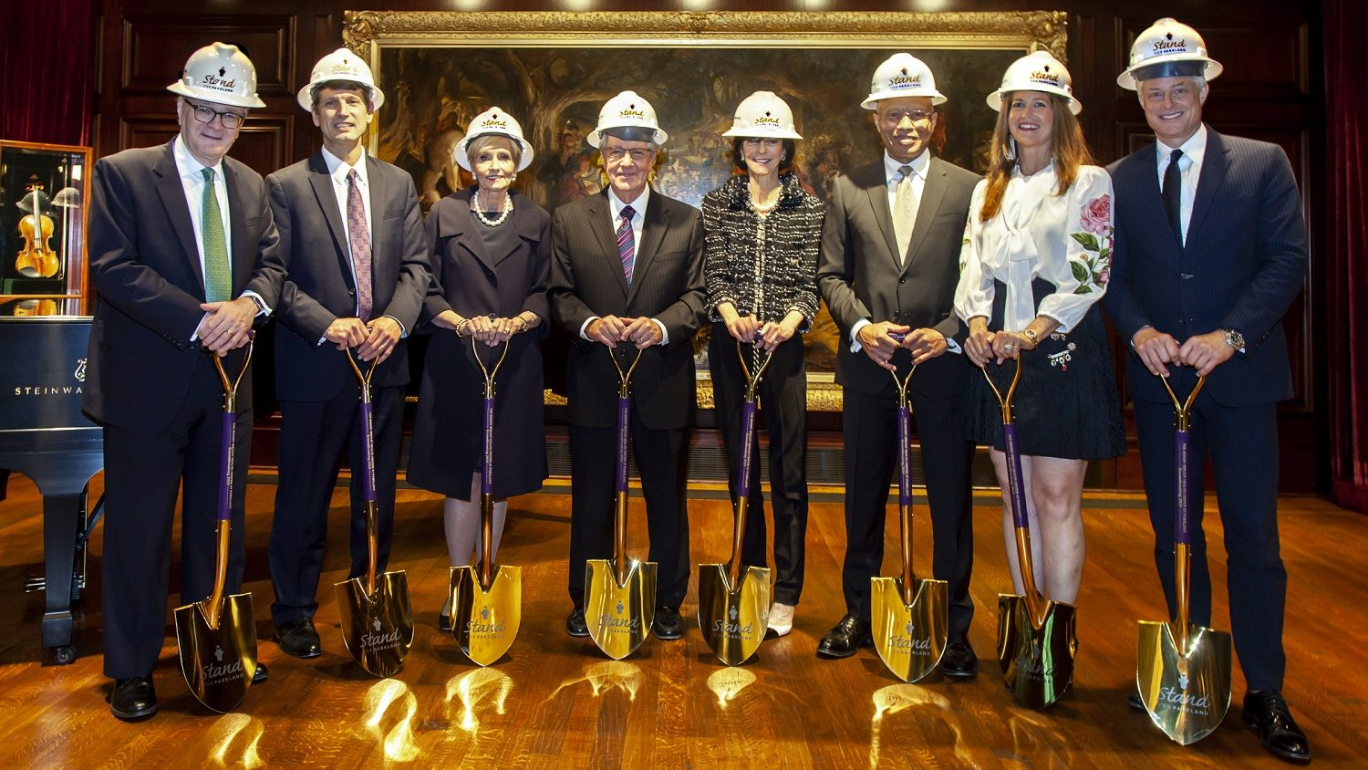 A group of people pose for the camera with shovels and hardhats