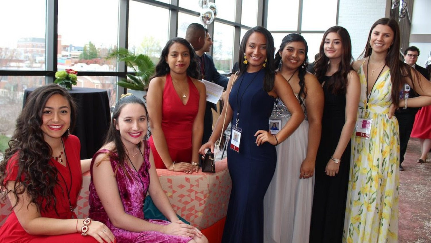 A group of people in formal dresses pose for the camera