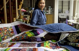 A person looks over a pile of quilts