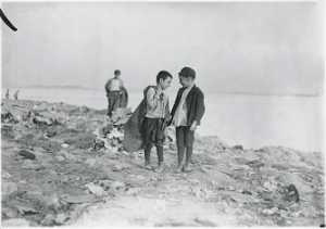 A photograph of two boys standing on a trash pile