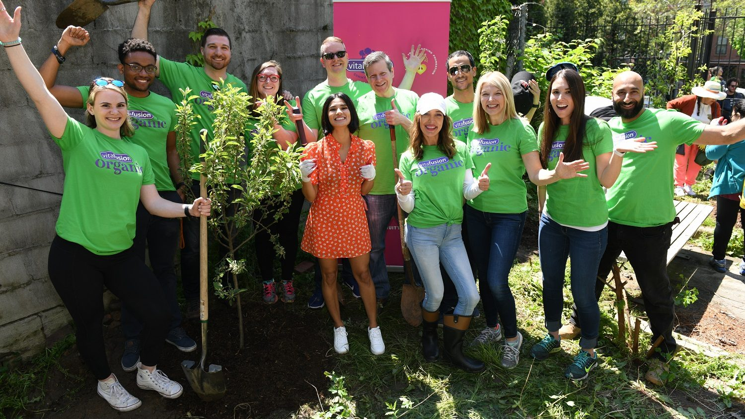 A group of people in green shirts pose for the camera holding gardening tools