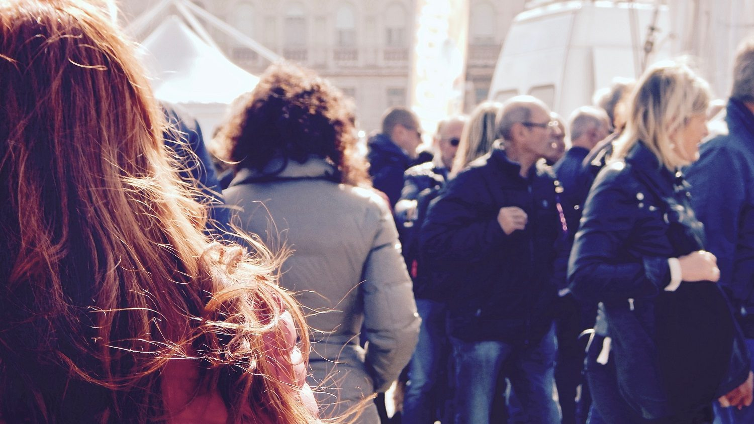 Person with red hair looks into a crowd of people