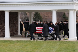 A group of people in suits carry a casket with an American flag draped over it