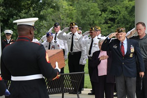 A group of soldiers salute a veteran's remains