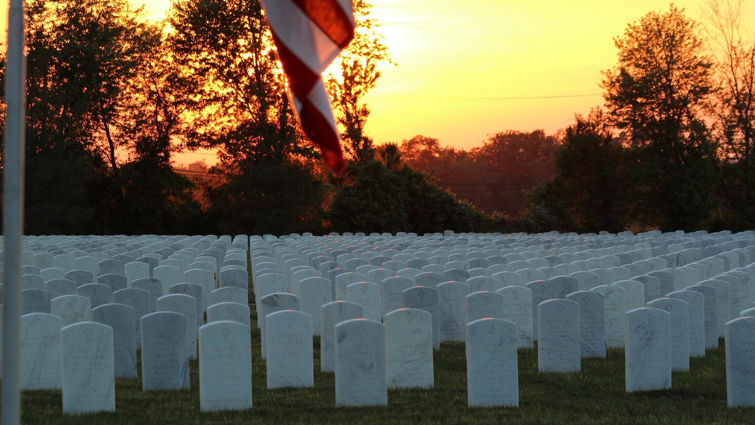 A field of grave stones with a sunset in the background