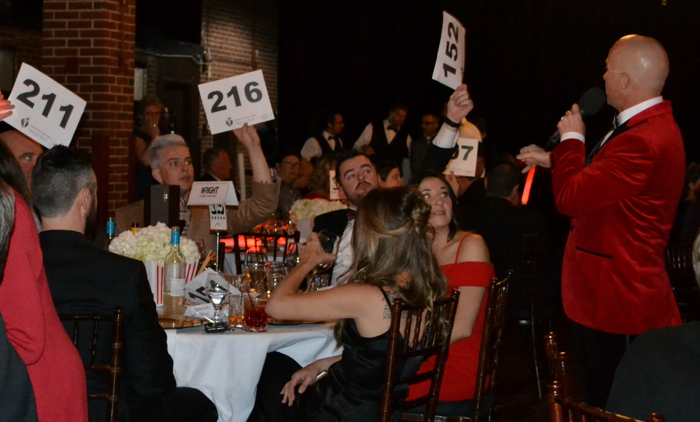 A group of people sitting at a table hold up signs with numbers on them