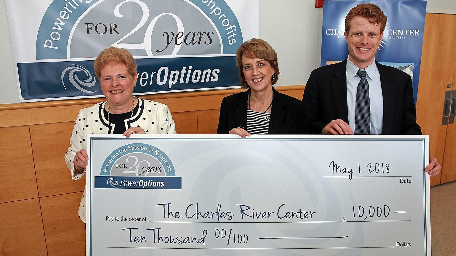 Three people pose with a large check