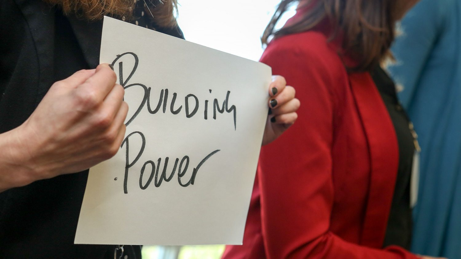 "A person holds a sign that says ""Building Power"""