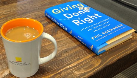 "CEP mug with coffee next to Phil Buchanan's book ""Giving Done Right"""