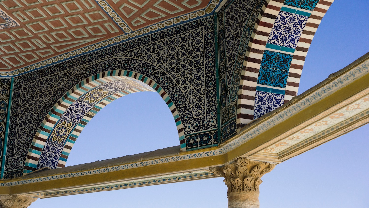 Arches with blue, green, and gold mosaic tiles