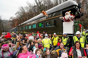 A man dressed as Santa passes out toys to a large crowd from the back of a train.