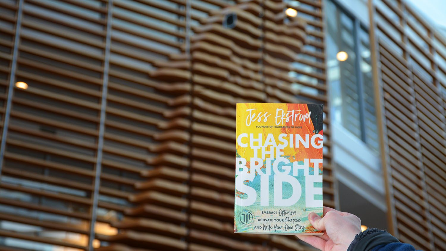 """Chasing The Bright Side"" book held in air in Talley Student Union"