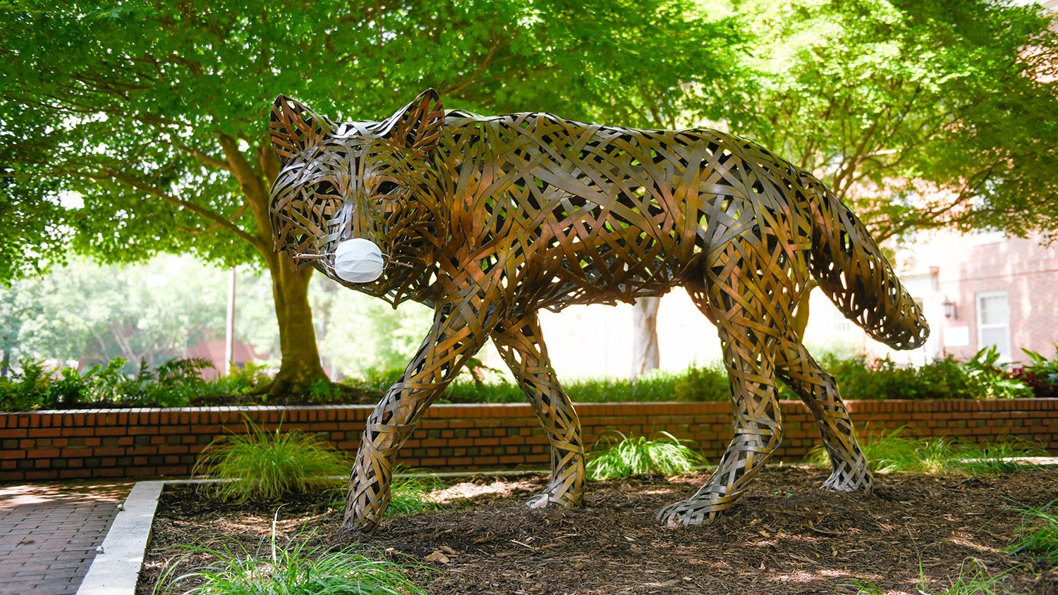 copper wolf statue wearing mask
