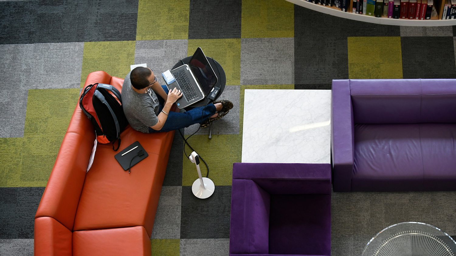 aerial view of student sitting with laptop in library