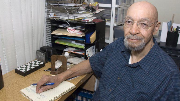Poet Gerald Barrax sits at his desk.