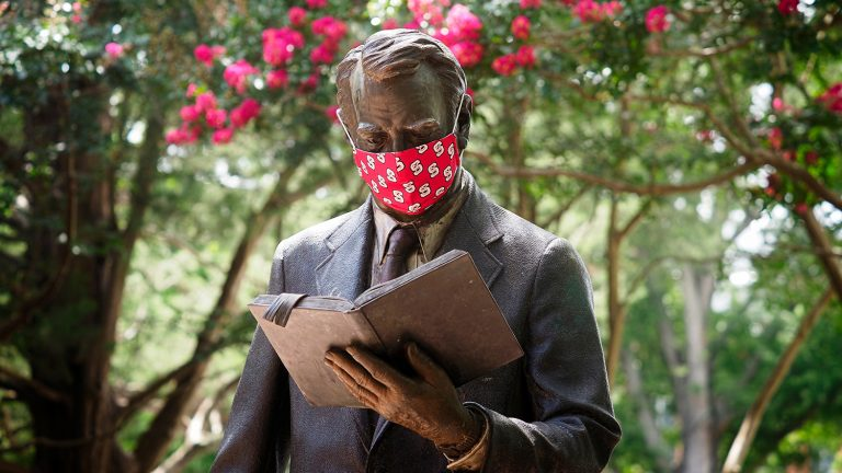 strolling professor statue wearing mask