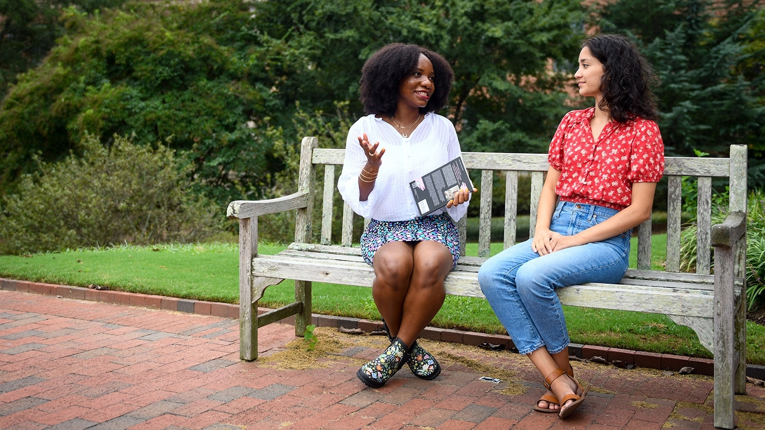 Rafeeat Aliyu and Meghan Tanaka sit beside each other on a bench on campus and discuss creative writing.