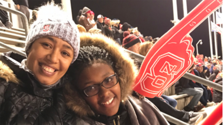 mom and daughter sit in stands at football game