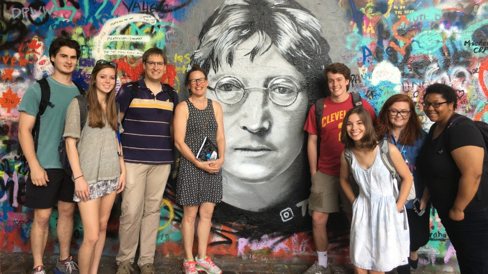 Teachers and students stand in front of the John Lennon wall in Prague.