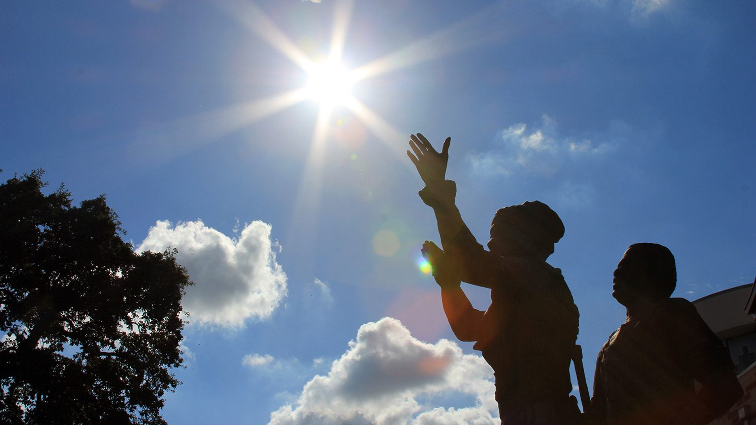 statues of a man and woman silhouetted against the sun